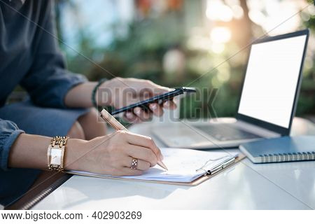 Selective Focus Of Hand Young Asian Woman Use Pen Checklist On Paperwork Of Investment While She Wor