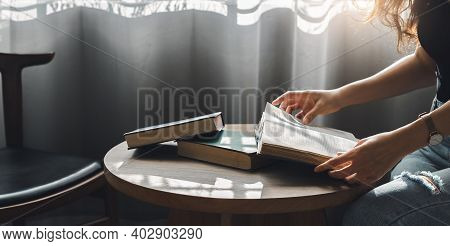 Crop Shot Of Young Asian Woman Open And Reading Old Book On Wooden Table In Living Room