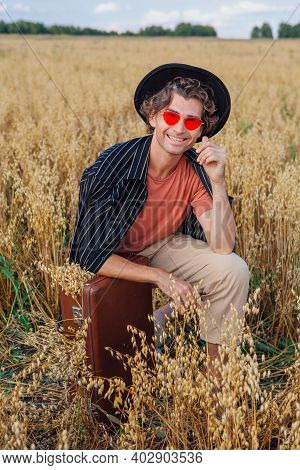 Tall Handsome Man With Brown Suitcase Full Of Ears Of Oats Sitting At Golden Oat Field.