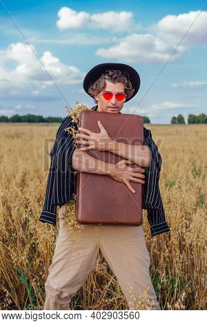Tall Handsome Man Hugging Brown Suitcase Full Of Ears Of Oats At Golden Oat Field.
