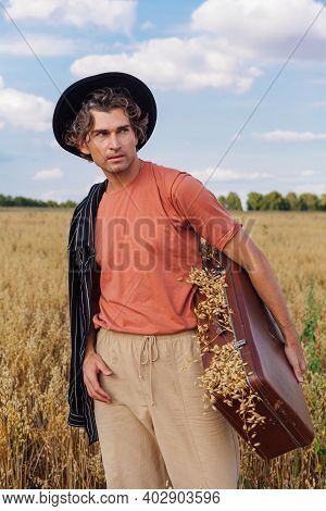 Tall Handsome Man Holding Brown Suitcase Full Of Ears Of Oats At Golden Oat Field.