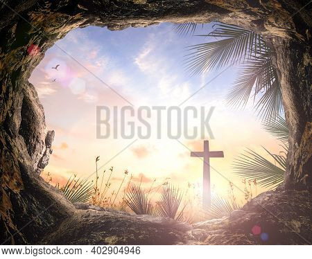 Palm Sunday Concept: Silhouette Cross And Empty Tombstone With Palm Leaves Over Meadow Sunset Backgr