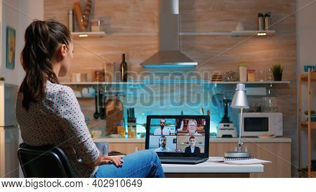 Businesswoman On Video Conference Working Remotely From Home Sitting In The Kitchen Late At Night. L