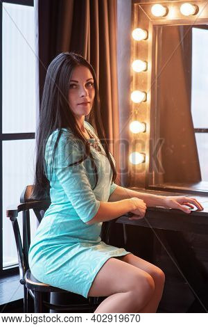 Beautiful Young Woman Sitting Near Dressing Table At Home. Beautiful Brunette In A Dress