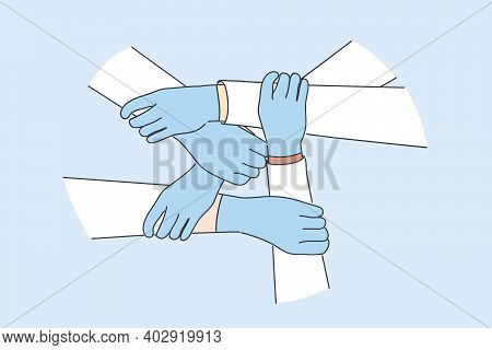Medical Teamwork, Health Worker Unity Concept. Hands Of Doctors In Protective Gloves Holding Each Ot
