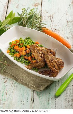 chickens wings with carrots and green peas salad