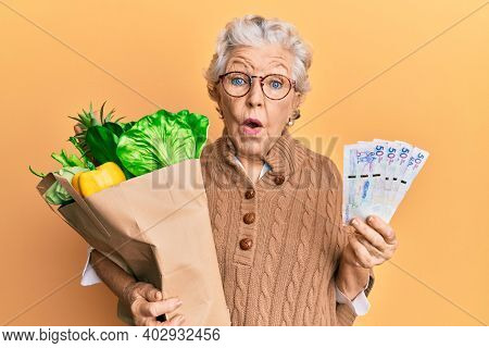 Senior grey-haired woman holding groceries and colombian pesos banknotes in shock face, looking skeptical and sarcastic, surprised with open mouth