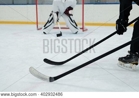 Hockey sticks held by two players in skates, gloves and sports uniform on background of goal keeper getting ready to catch puck