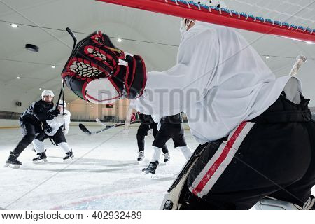 Back view of hockey player in sports uniform and gloves standing in the net in front of group of rivals and preparing to catch puck