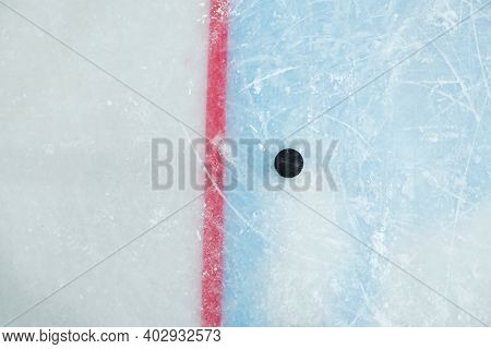 Black puck lying by red line on ice rink for playing hockey on stadium that can be used as background for sports advertisement or announcement