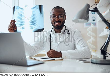 Satisfied Therapeutist Is Showing An X-ray Film