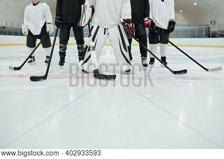 Low section of several hockey players and their trainer in sports uniform, gloves and skates standing on ice rink at stadium and holding sticks