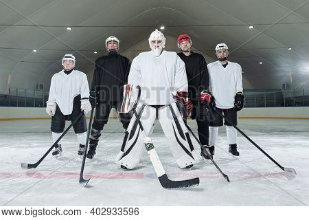 Professional hockey players and their trainer in sports uniform, gloves, skates and helmets standing on ice rink and waiting for start of play