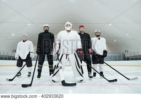 Several hockey players and their trainer in sports uniform, gloves, skates and helmets standing on ice rink and holding sticks in front of themselves