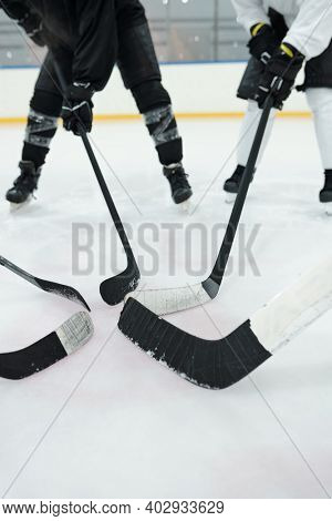 Several professional hockey players in sports uniform, gloves and skates standing in circle on ice rink and holding their sticks in front of themselves