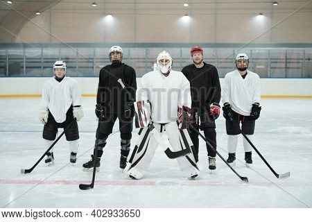 Professional hockey players and their trainer in sports uniform, gloves, skates and protective helmets standing on ice rink while waiting for play