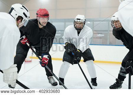 Group of professional young hockey players and their trainer in sports uniform, protective helmets, gloves and skates training before play