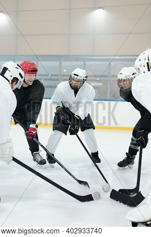 Group of professional hockey players in sports uniform, protective helmets, gloves and skates standing in circle on ice rink during training before play