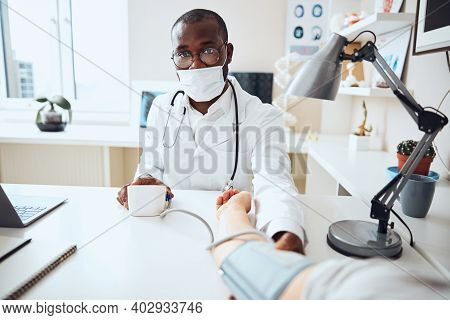 Therapeutist Pressing The Button On An Electronic Blood Pressure Monitor