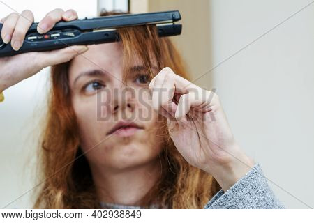 Woman Using A Hair Straightener To Straighten Her Hair