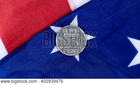 A 25 Cent American Dollar Coin Lies On The American Flag. The Currency Is One Cent Over The Flag Of