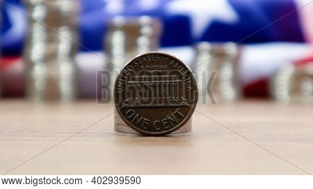 A 1 Cent American Dollar Coin Lies On The American Flag. The Currency Is One Cent Over The Flag Of T