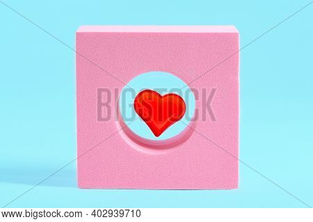Valentine's Day Concept With A Red Heart In An Abstract Pink Figure On A Light Blue Background With