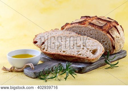 Sliced Artisanal Organic Sourdough Bread, Olive Oil And Fresh Rosemary On A Textured Background With