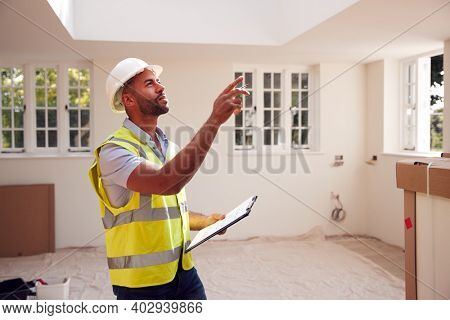 Building Surveyor Wearing Hard Hat With Clipboard Looking At Interior Of New Property
