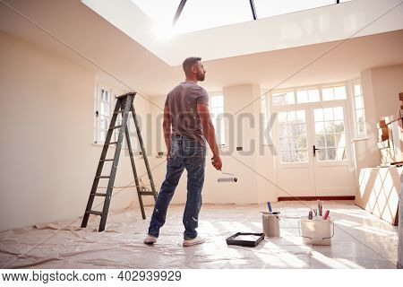 Rear View Of Man Holding Paint Roller Decorating New Home