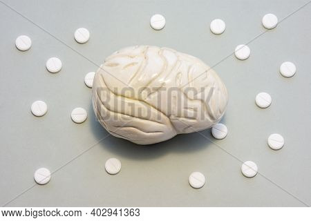 Brain On Gray Background With Tablets In Pattern Of Polka Dots. Photo Denoting Brain Gray Matter, Tr