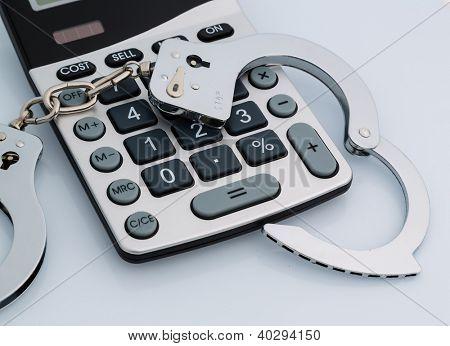 Taschenrechner und Handschellen auf weißem Hintergrund. Repräsentative Foto von Wirtschaftskriminalität