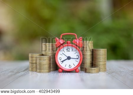 A Red Alarm Clock On A Coin Financial Concepts, Savings, Investments In Finance, Accounting And The