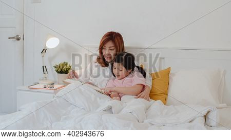 Asian Grandmother Read Fairy Tales To Granddaughter At Home. Senior Chinese, Grandma Happy Relax Wit