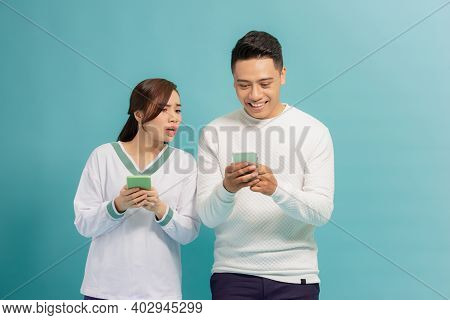 Young man and woman are typing on their mobile phones. Woman is looking at his boyfriend\'s phone