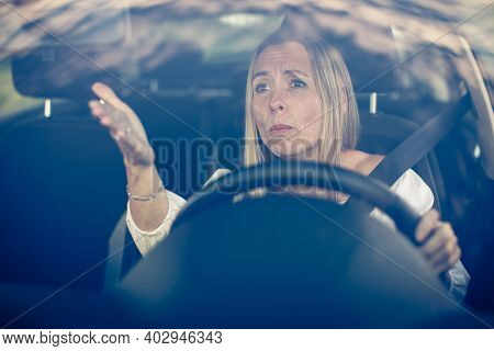 Middle aged woman at the steering wheel of her car, getting angry