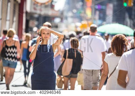 Pretty, young businesswoman talking on the phone while walking in Downtown Manhattan (shallow DOF; color toned image)