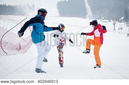 Group Of Friends Wearing Vivid Ski Suits Warming Up Before Skiing From Piste In Mountains In Winter.