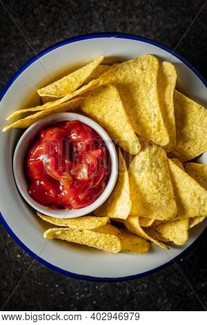 Tortilla chips and red tomato salsa dip. Mexican nacho chips on black table. Top view.