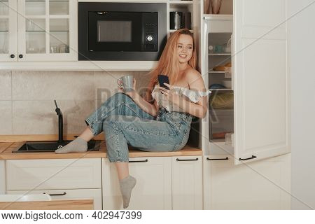 A Woman Is Sitting At Home In The Kitchen At The Will Of The Refrigerator. A Girl With A Good Figure