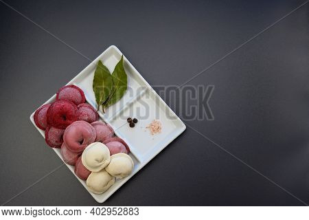 Red, Pink And White Frozen Homemade Dumplings And Spices In A Square Plate On A Gray Background. Hom