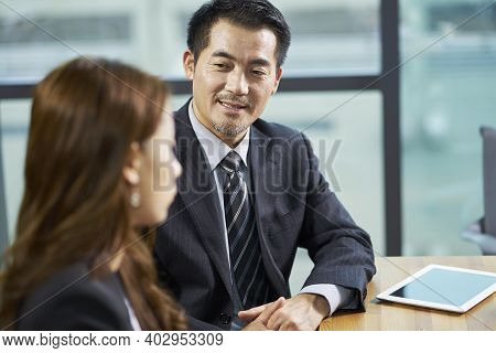 Two Asian Corporate Executives Having A Conversation In Office