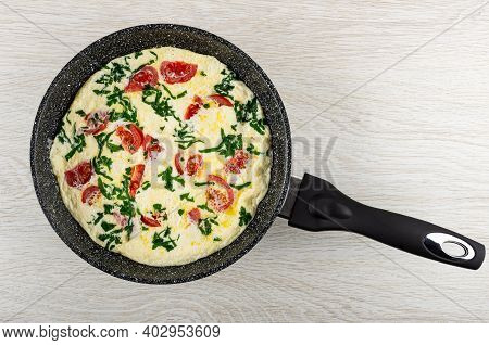 Omelette With Tomato And Parsley In Frying Pan On Wooden Table. Top View