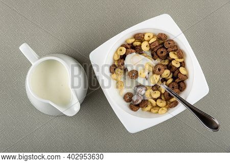 Pitcher With Yogurt, Spoon In White Bowl With Toasted Cereal Breakfasts And Yogurt On Gray Table. To