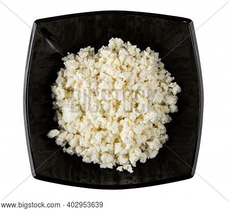 Black Glass Bowl With Defatted Grainy Cottage Cheese Isolated On White Background. Top View