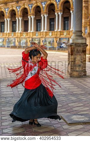 Passionate Flamenco Dancer Woman In Colorful Clothes Dancing At The Plaza De Espana In Seville
