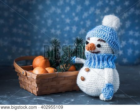 Crocheted White Snowman In A Blue Hat With A Branch Of A Christmas Tree And A Basket With Tangerines