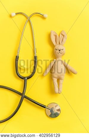Simply Minimal Design Toy Bunny And Medicine Equipment Stethoscope Isolated On Yellow Background. He