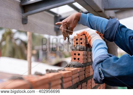 Close Up Hand Of Bricklayer Worker Installing Brick Masonry On Exterior Wall With Trowel Putty Knife