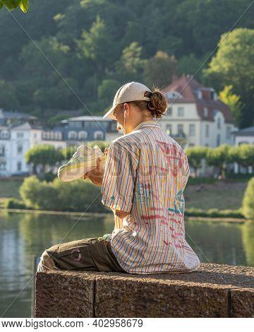Heidelberg, Germany - Aug 1, 2020: Artist Paint Grafitti On Shoe On Heidelberg Bridge